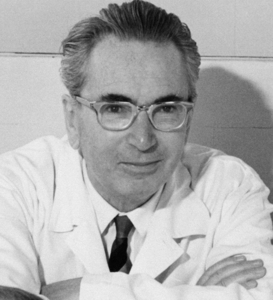 This is a black and white photograph taken of Viktor Frankl in 1965. He is wearing a white labratory coat, a collared shirt and a tie. He has his arms crossed out in front of him as he leans on a table to pose for the picture.